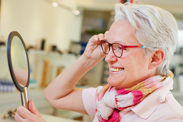 Elderly woman with glasses looking in mirror