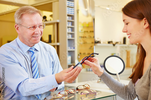 Optician selling glasses to customer