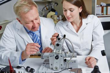 Woman as apprentice in optician workshop