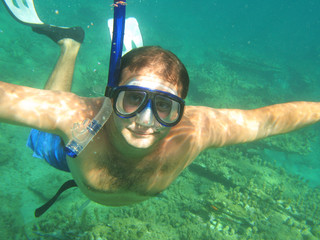 man wearing a mask and flippers dives into the sea with pleasure