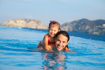 Father  with his daughter swimming in pool