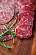 Salami and rosemary on wooden chopping board