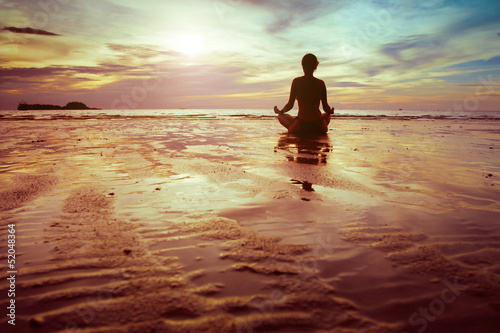 sport and fitness, silhouette of woman meditating on the beach