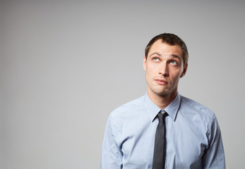 Handsome young business man thinking against gray background
