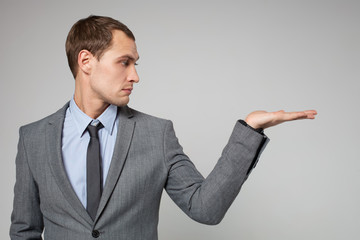 young business man holding something imaginary in his hand and l