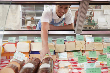 Sales Clerk reaching in to get cheese at Deli counter
