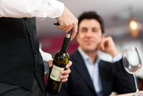 Waiter serving wine to a customer