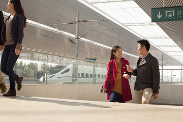 Young woman talking to man on railway platform, China