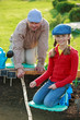 Gardening, sowing - girl helping father in the garden