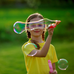 Summer joy, young girl playing with soap bubbles