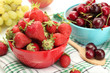 Ripe strawberries and cherry berries in bowls, grapes and apple