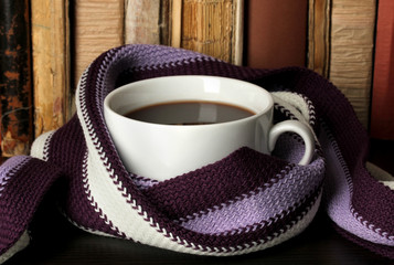 Cup of coffee wrapped in scarf on books background