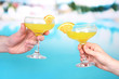 Cocktails in men's and women's hands on pool background