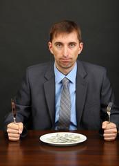 Young businessman having dinner dollars on black background
