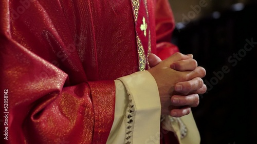 Portrait of happy catholic priest smiling on altar in church