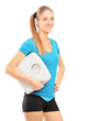 A smiling female athlete holding a weight scale and looking at c