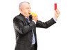 A mature businessman blowing a whistle and showing a red card