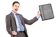 A happy young businessman holding a briefcase and gesturing happ