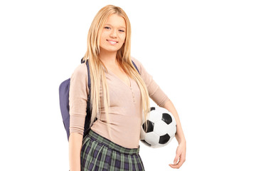 A young female student with bag holding a soccer ball
