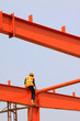a worker working on red steel beam