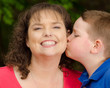 Happy mother laughing at kiss from son