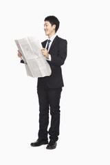 Businesswoman reading newspaper