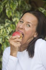 Happy mature woman eating apple