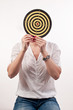 Young woman with dartboard in front of face, Bull's Eye