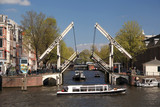 Amsterdam with boat against old bridge in Holland