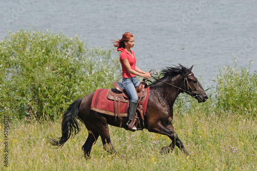 Equestrian woman horseback riding on beach
