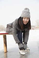 Young woman putting on ice skate, Beijing