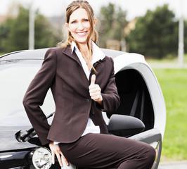 Lächelnde Geschäftsfrau vor einem Elektromobil