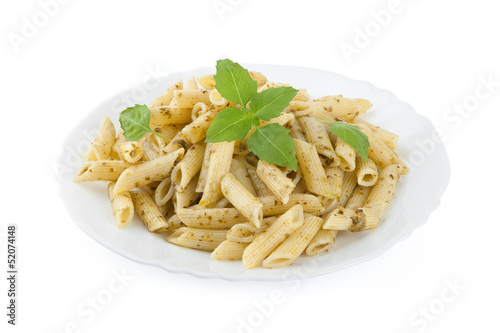 Pasta with pesto sauce and fresh basil on white plate