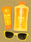 Bottle and tube of sunscreen and yellow sunglasses on sand