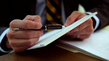 бизнесмен с ручкой и бумагами крупным планом