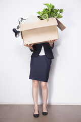 Young Businesswoman holding box of office items