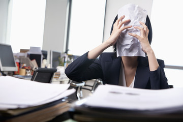 Young businesswoman sitting at desk covering her face with a paper