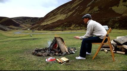 man sitting around camp fire wanlockhead scotland
