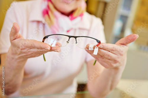 Hands of optician offering glasses