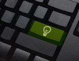 Green energy key with bulb light icon on  keyboard.