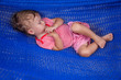 Little baby girl asleep outdoors on a hammock
