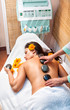 Stone therapy. Woman getting a hot stone massage in spa salon
