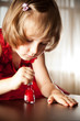 Little girl in a red dress painted nails with nail polish