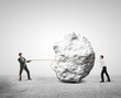 two businessman pulling a rope rock