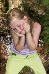 Little girl sitting on  tree