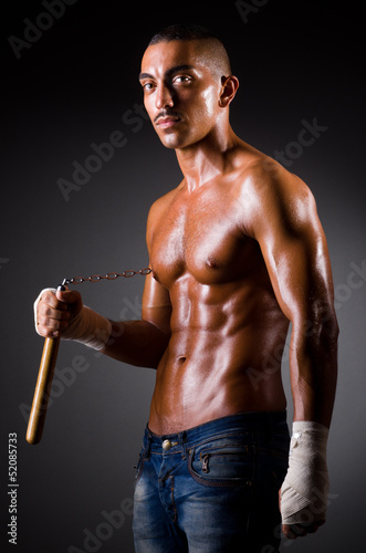 Muscular man with nunchucks on white