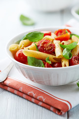 Penne with roasted cherry tomatoes and basil leaves