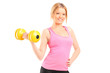 An attractive young woman lifting a dumbbell