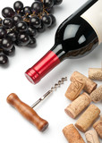 Bottle of red wine, grapes, corkscrew and corks on white