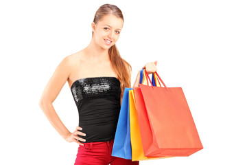 A young smiling female holding shopping bags and posing